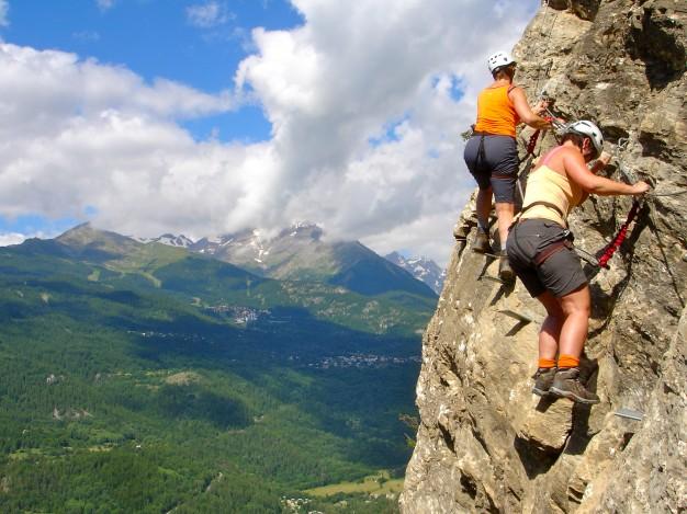 Dans la via ferrata des vigneaux avec les guides de Serre Chevalier. Au fond : Puy Saint Vincent, Vallouise, Hautes Alpes.
