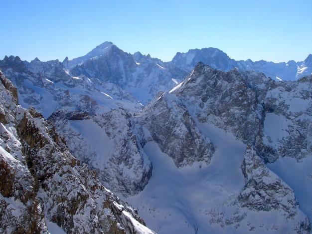 Descente hors piste sur la Selle, depuis le Dôme de la Lauze (3567 m). Au fond, la Barre des Ecrins, les Ailefroides et les Bans. Free ride à la Grave, avec les guides de Serre Chevalier.